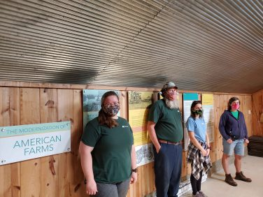 Farm staff standing in front of interpretive panels.